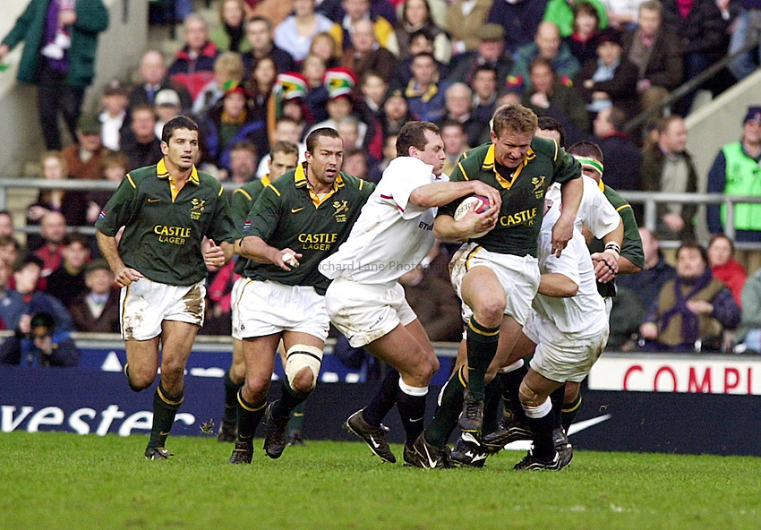 Photo. Richard Lane. .England vs South Africa - Twickenham. 02.11.00.Andre Venter, With team mates Krige and Westhuizen in close attendance, tries to take on Englands Richard Hill.