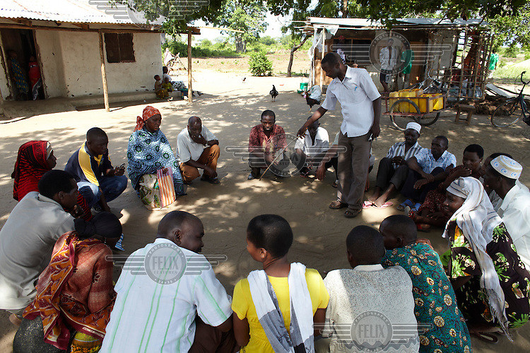 Chairperson Zuberi Kijoga points to a diagram drawn in the sand as he stands in the middle of a circle of villagers during a meeting.