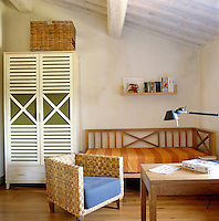 A child's bedroom has a free-standing cupboard and wicker baskets for storage with a simple wooden bed in one corner
