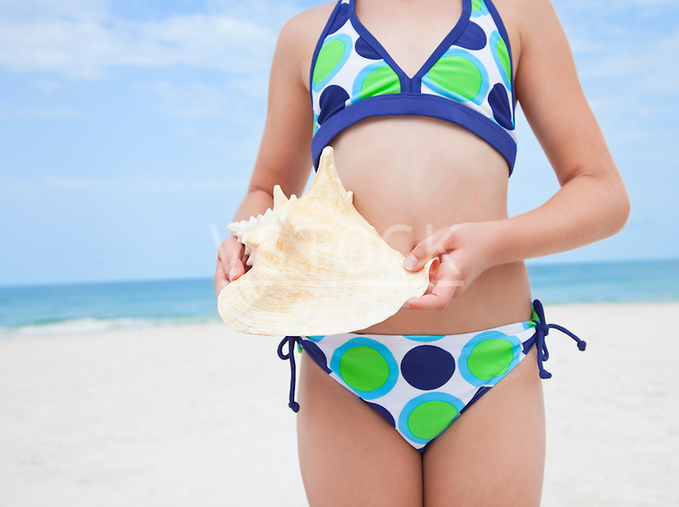 USA, Florida, St. Pete Beach, Girl (8-9) holding conch shell on beach, mid section