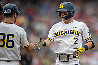 Michigan Wolverines shortstop Jack Blomgren (2) is greeted by first base coach Michael Brdar )36) during Game 1 of the NCAA College World Series against the Texas Tech Red Raiders on June 15, 2019 at TD Ameritrade Park in Omaha, Nebraska. Michigan defeated Texas Tech 5-3. (Andrew Woolley/Four Seam Images)