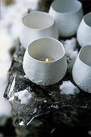 A small group of tealights in delicate porcelain holders on an ice-covered step