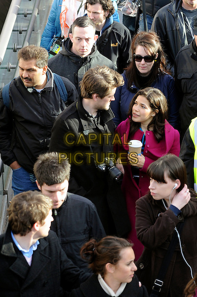 AMERICA FERRERA.filming 'Ugly Betty' on location at The Millenium Bridge, London, England, UK,.5th April 2010..filmset film set half length coffee cup drink pink red coat crowd .CAP/IA.©Ian Allis/Capital Pictures.