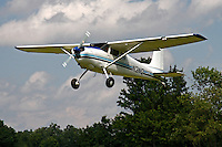 A white Cessna 190F with blue and navy detailing ascends over the tree tops into a cloud filled sky at the 2010 Wings 'n' Wheels Showcase.