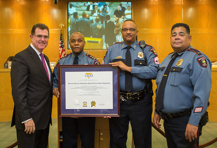 L-R: Houston ISD Superintendent Dr. Terry Grier, HISD Chief of Police Jimmy Dotson, Sgt. DL Moore and Lt. R. Barrera pose for a photograph following the presentation of a certificate of accreditation from the Commission on Accreditation for Law Enforcement Agencies during the Board of Education meeting, October 10, 2013.