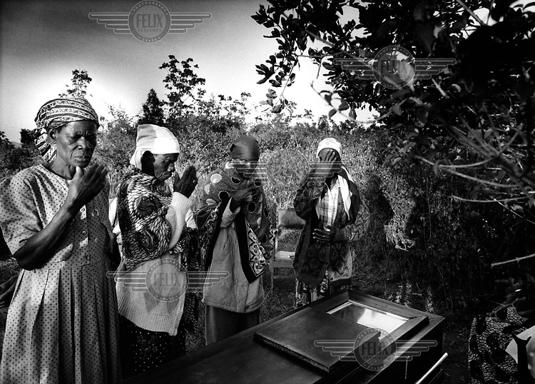 A funeral in the Luo community. Jarred Apamo has died of AIDS, and his body has been transported to his rural birthplace according to tribal tradition. Relatives pay their respects at his coffin.