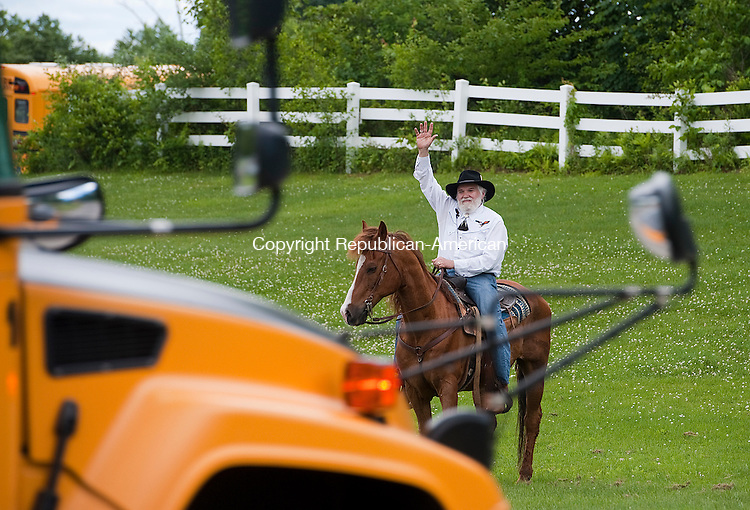 TORRINGTON, CT-061814JS02--Torrington Middle School teacher Matthew Valenti, who is retiring after 40 years, waves goodbye to students while sitting atop his horse Calypso Jack on the last day of school on Wednesday. <br />  Jim Shannon Republican-American