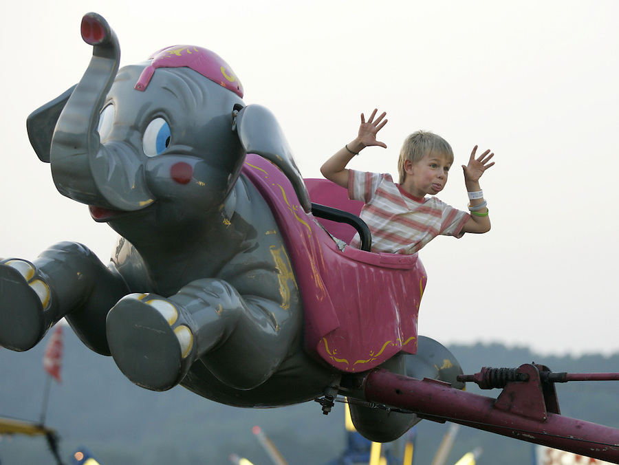 Dylan Hahn makes a funny face to friends below while riding high on the dumbo ride Thursday at the Albemarle County Fair. Photo/Andrew Shurtleff