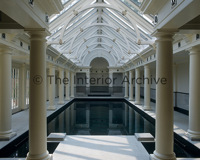 The glass roof of this impressive indoor swimming pool is supported by rows of Doric columns