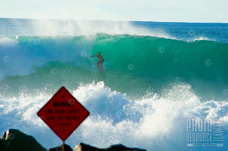 "Man riding a wave with sign reading """"dangerous surf"""" our of focus in the foreground."