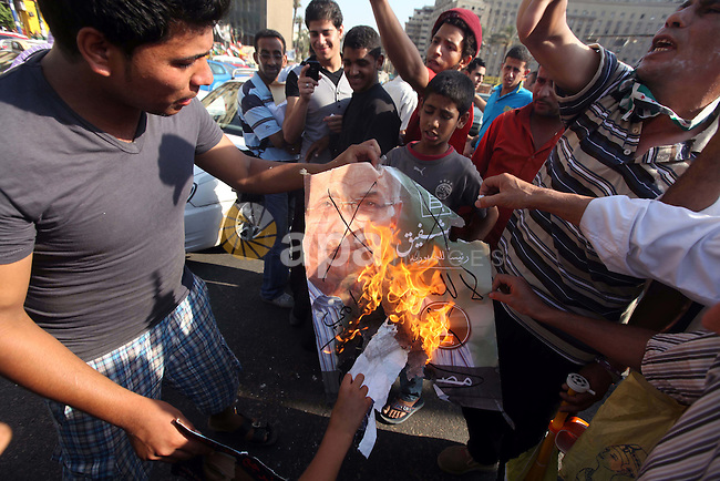 Egyptian protesters burn a placard against presidential candidate Ahmed Shafik during a protest at Cairo's Tahrir square, Egypt, 14 June 2012. Media reports on 14 June state that the Supreme Constitutional Court ruled that Ahmed Shafik could stand in the presidential election run-off, saying a law banning officials who served under Hosni Mubarak from running for office was unconstitutionall. Photo by Majdi Fathi