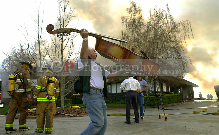 Dillon Crandall moves an upright bass out of harm's way as firefighters work to extinguish a house fire on El Alamo Way in Danville, Calif., Tuesday morning Feb. 25, 2003. Most of the second story was destroyed by flames. Danville police estimated the danage of the home at $3 million.  Alan Greth/ Contra Costa Times)