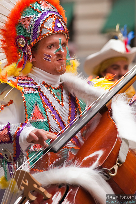 A mummer smokes a cigarette, while playing his bass and marching up Broad Street in the 2006 Philadelphia Mummer's Parade.