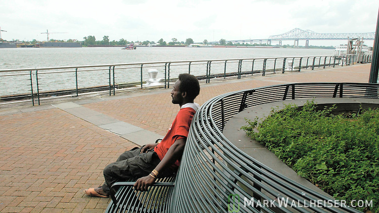 "A homeless resident of New Orleans, Louisiana sits on the levee in Woldenberg Riverfront Park on the  Mississippi River August 28, 2005 and waits on Hurricane Katrina.    When asked about the strong category 5 approaching hurricane he said, ""I'll be in the hands of the Lord.""  Hurricane Katrina killed seven when she made her first landfall in south Florida as a category 1 storm and has set her sights on this tourist city that was built below sea level."