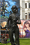 Statue of Charlie Chaplin seen against colourful posters in Leicester Square, London, England