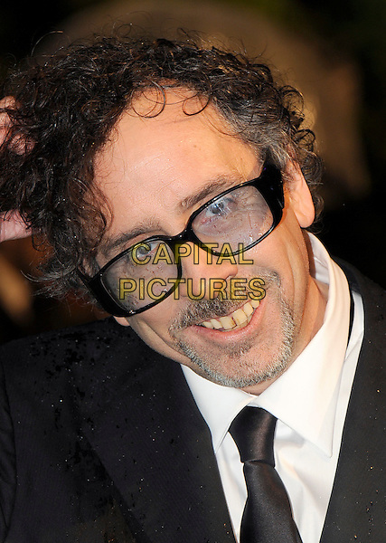 TIM BURTON .Royal World Film Premiere of 'Alice in Wonderland' at the Odeon cinema, Leicester Square, London, England, UK, 25th February 2010 .arrivals portrait headshot glasses tinted black tie smiling teeth goatee facial hair beard .CAP/BEL.©Tom Belcher/Capital Pictures.