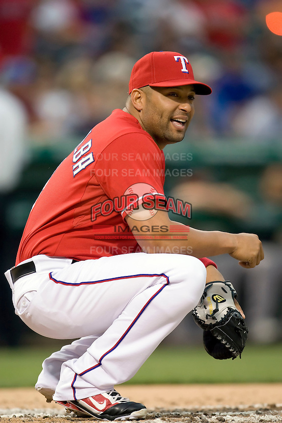 Texas Rangers catcher Yorvit Torrealba (8) warms up the pitcher in between innings against the Oakland Athetics in American League baseball on May 11, 2011 at the Rangers Ballpark in  Arlington, Texas. (Photo by Andrew Woolley / Four Seam Images)