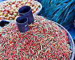 Chili peppers and tomatos are displayed in baskets with cups for measuring portions for sale in the main market of Bitung, North Sulawesi, Indonesia.