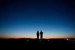 A silhouetted couple looks at the post-sunset sky as friends gather to play in the sand and surf of the Atlantic Ocean shoreline during the 21st annual Sacrifice Your Body (SYB) beach party at the Assateague Island National Seashore in Berlin, Maryland, on July 3, 2010. The photo was made during a Miller-Stute family vacation to the East coast.