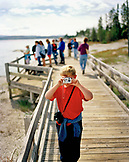 USA, Wyoming, boy photographing with tourists standing in the background, West Thumb Geyser Basin, Yellowstone National Park