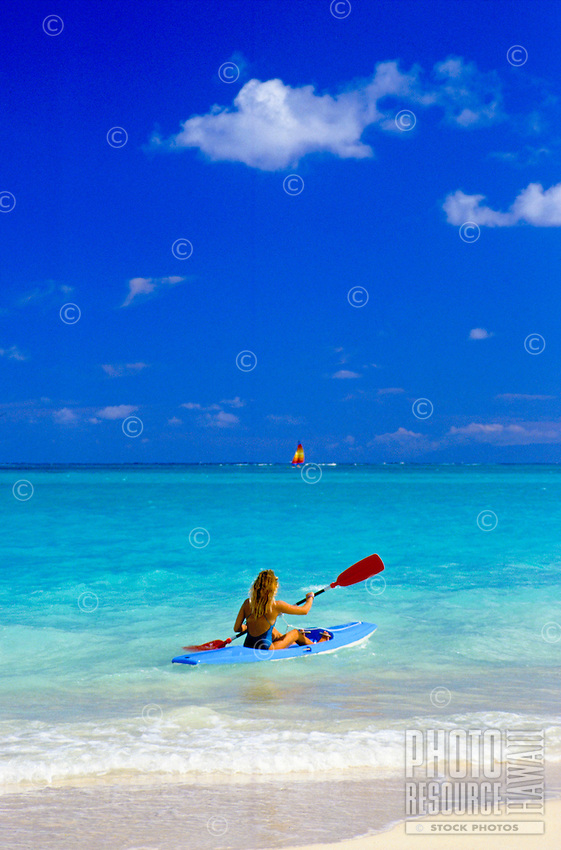 A woman kayaks in the famous turquoise waters off Lanikai Beach on the windward side of Oahu.