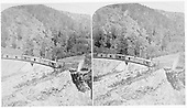A D&amp;RG freight train halted for the photographer with the conductor seated on the pilot and a couple of brakemen atop a boxcar, on Mule Shoe Curve - La Veta Pass.<br /> D&amp;RG  La Veta Pass, CO  Taken by Gurnsey, B. H. - ca. 1877
