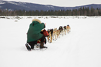 Peter Bartlett kneels on his runners as his team runs down the Kuskokwim river shortly before McGrath on Wednesday during the 2008 Iditarod