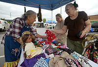 NWA Democrat-Gazette/BEN GOFF @NWABENGOFF<br /> Linda Woods (from left) of Linda's Clothes Line from Rogers, shows some of the doll and pet clothes she makes to Angela Russell and her mother Mary Blake of Bella Vista Sunday, June 18, 2017, during the Bella Vista Farmers Market in the parking lot of Mercy Bella Vista.