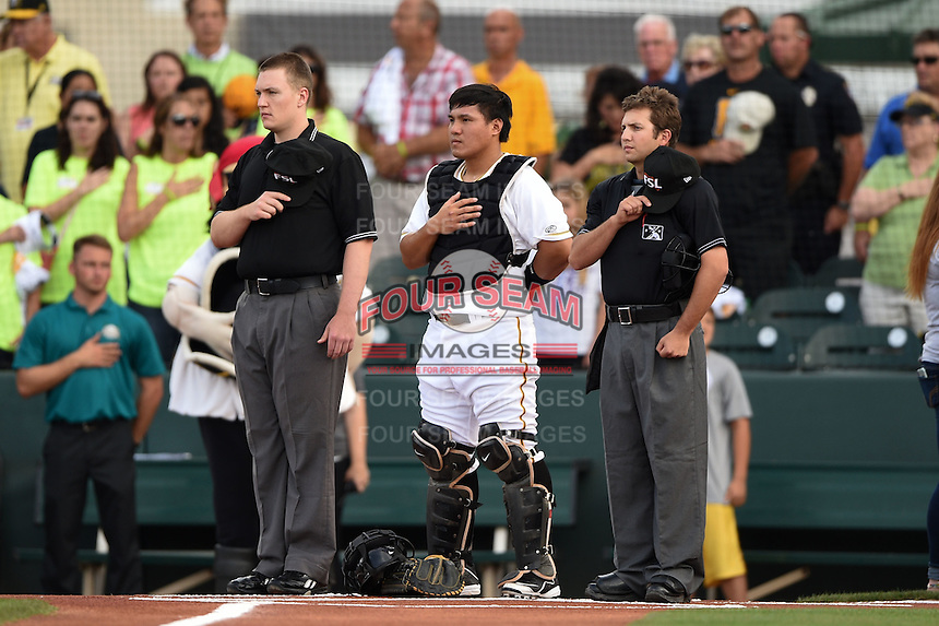 Bradenton Marauders catcher Jin-De Jhang (47) stands with umpires Dave Attridge (left) and Joe George during the national anthem before a game against the Jupiter Hammerheads on April 17, 2015 at McKechnie Field in Bradenton, Florida.  Bradenton defeated Jupiter 11-6.  (Mike Janes/Four Seam Images)