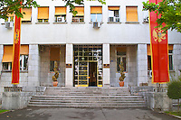 Skupstina Republica Crna Gora, the parliament assembly of Montenegro, main entrance with glass, brass and stone, on the Sveti Petra Saint Peter boulevard. Montenegrin banner flag in red with eagle Podgorica capital. Montenegro, Balkan, Europe.