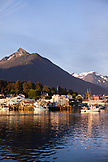 USA, Alaska, Sitka, a peaceful view of homes and fishing boats along the shore in Sitka Harbor at sunset, Mount Verstovia peak in the distance