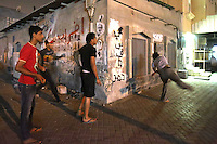 Photographer: Rick Findler..21.04.13 Protesters throw stones at riot police front lines of a clash between police and protesters in Ma'ameer, Bahrain. The number of protests in Bahrain increase dramatically during the sporting event to help bring attention to the ruling bahraini Sunni royal family's many human rights abuses and repression of the country's Shiite people.