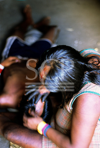 Bacaja village, Amazon, Brazil. Mother with bleeding scalp removes stings from son; hornets' nest initiation ceremony; Xicrin.