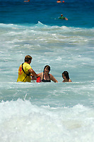 lifeguard assist a mother and daughter during large surf at Magic sands beach Kailua Kona The Big Island of Hawaii