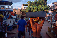 A porter hauls bananas off of a boat docked on the Rio Negro at Manaus, Brazil, Monday, Jan. 9, 2006. With few roads leading to the outside world, most goods are brought to the city 1,000 miles inland from the coast by boat. (Kevin Moloney for the New York Times)