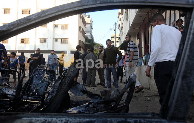 "Palestinian gather arround a destroyed car following an Israeli strike in Gaza City on November 20, 2012. Israel's air force dropped leaflets across several districts of Gaza City urging people to evacuate their homes ""immediately"" amid fears of an imminent ground invasion. Photo by Majdi Fathi"