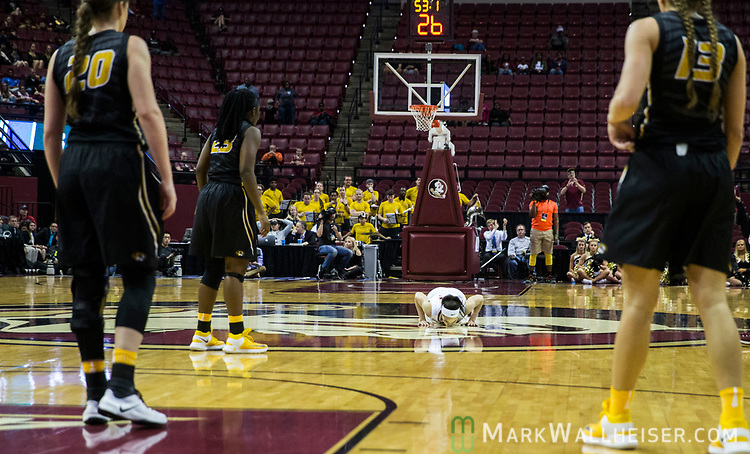 Missouri watches as Florida State guard Brittany Brown bends down and kisses the Florida State logo with 53 seconds left in her last home game of a second-round game of the NCAA women's college basketball tournament in Tallahassee, Fla., Sunday, March 19, 2017. Florida State defeated Missouri 77-55. (AP Photo/Mark Wallheiser)