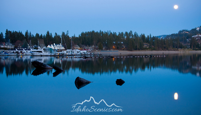 Idaho, Coeur d'Alene. Moonrise over Sanders Beach Marina reflected in the water of Lake Coeur d' Alene.