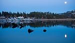Idaho, Coeur d'Alene. Moonrise over Sanders Beach Marina reflected in the water of Lake Coeur d' Alene.