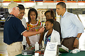 Terry White, United Space Alliance project lead for thermal protection systems, left, shows United States President Barack Obama and his family, from left, First Lady Michelle Obama, Malia, Marian Robinson and Sasha, how tiles work on the space shuttle during their visit to the Orbital Processing Facility at the NASA Kennedy Space Center in Cape Canaveral, Florida, Friday, April 29, 2011..Mandatory Credit: Bill Ingalls / NASA via CNP