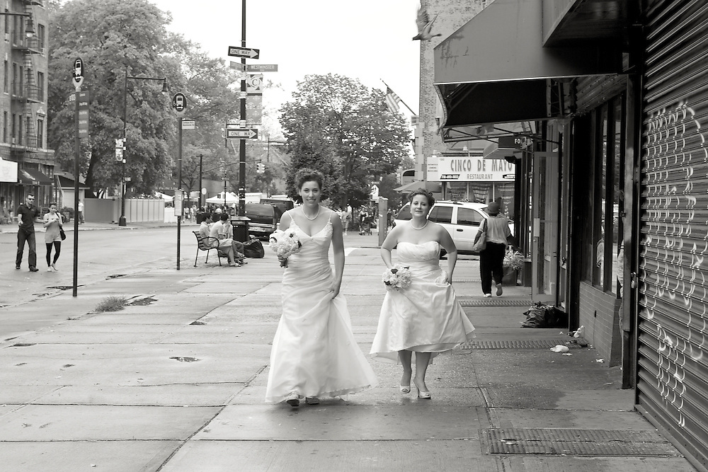 Black & white sepia photo of the two brides walking down the street.