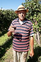 Raccolta dell'uva ai vigneti dei signori Franchini presso Montescano (Pavia) nell'Oltrepò Pavese. Nella foto: l'agricoltore con un bicchiere di vino rosso Bonarda da lui prodotto --- Grape harvest at Franchini's vineyards near Montescano (Pavia) in the Oltrepò Pavese. In the picture: the farmer with a glass of his Bonarda red wine