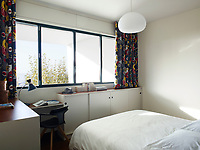 In the bedroom, custom built cupboards with sliding doors provide storage and working space whilst the chair is Patrick Norguet. The curtains are made from graphic Gaston y Daniela fabric.