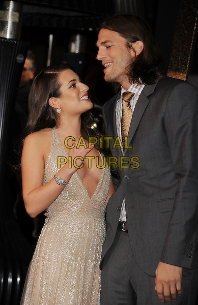 "Lea Michele & Ashton Kutcher.The World Premiere of ""New Year's Eve' held at The Grauman's Chinese Theatre in Hollywood, California, USA..December 5th, 2011.half length gold beige dress low cut plunging neckline cleavage grey gray suit jacket smiling funny profile .CAP/ROT/TM.©Tony Michaels/Roth Stock/Capital Pictures"