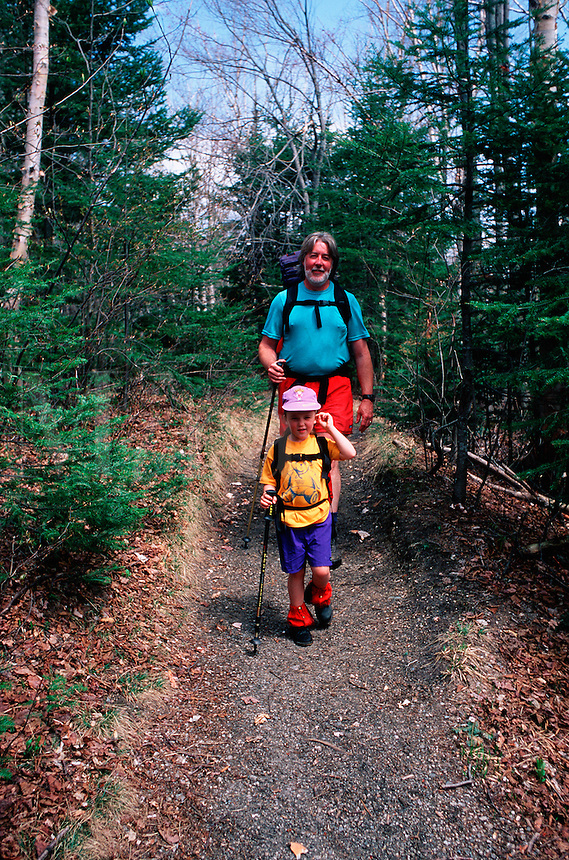 A father and young daughter take an easy hike along the trail leading to the Appalachian Mountain Club's Zealand Falls camping area. New Hampshire.