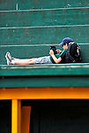 21 August 2010: Vermont Lake Monsters fan Josh Wolfstein relaxes over the dugout and checks out his dad's iPad prior to game action against the Brooklyn Cyclones at Centennial Field in Burlington, Vermont. The Cyclones defeated the Lake Monsters 8-7 in a 12-inning game that had to be resumed in Brooklyn on August 31 due to late inning rain. Mandatory Credit: Ed Wolfstein Photo