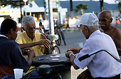 Sao Paulo State, Brazil. Group of old men playing cards at a street cafe, one smoking another taking a cigarette from a packet.