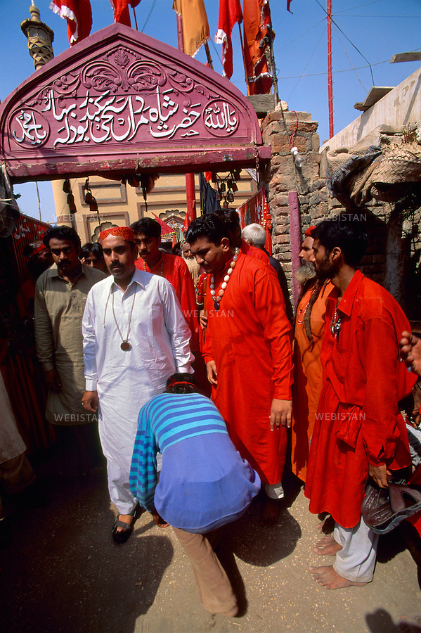 SEHWAN SHARIF, PAKISTAN - SEPTEMBER, 2006:  At the entrance of the shrine of Sufi Bodla Bahar, a devotee honouring the sufi master (pir), Sheikh Akhtar Hussein Pirzada, titled as  Noor Ali Shah, during the annual celebration of Urs of Lal Shahbaz Qalandar, a 13th century Sufi Master worshiped alike by Hindus and Muslims. Born as Seyed Shah Hussain (Usman) Marandi, he later on titled as Lal (red) Shahbaz ( Falcon) Qalandar (as he belonged to Qalandria order of sufism).
