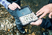 Fish Camp Manager Scott Tarrant shows off his tied fishing lures to Lois Friedland while fishing near Colorado Springs, Colorado, Monday, May 4, 2015. <br /> <br /> Photo by Matt Nager