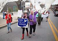 NWA Democrat-Gazette/CHARLIE KAIJO Marchers hold up signs during the Parade for Peace, Sunday, March 18, 2018 that started at the Walton Art Center and ended at the Town Center in Fayetteville. <br /><br />The Arkansas Poor People's Campaign, the OMNI Center and Arkansas Nonviolence Alliance held a Parade for Peace. The parade featured multiple floats, dancing troops and large art projects.